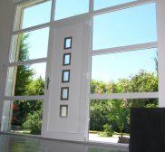 Installation moderne d'une porte pallière blindée avec vitres autour de la porte